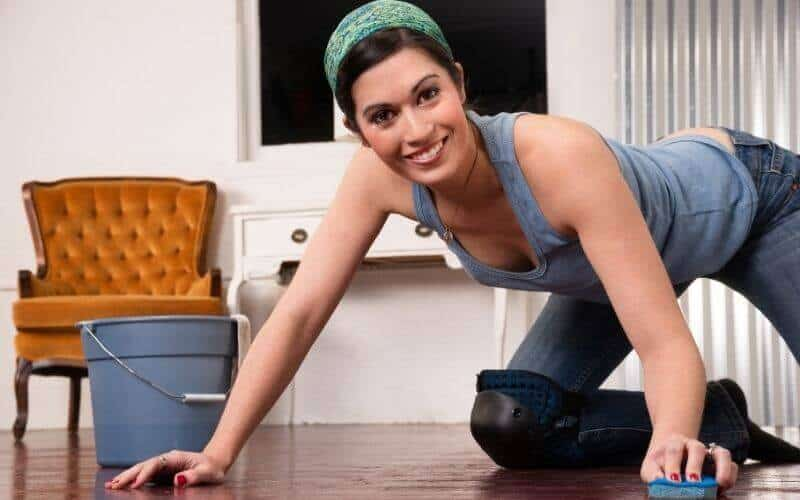 happy lady cleaning wood floor