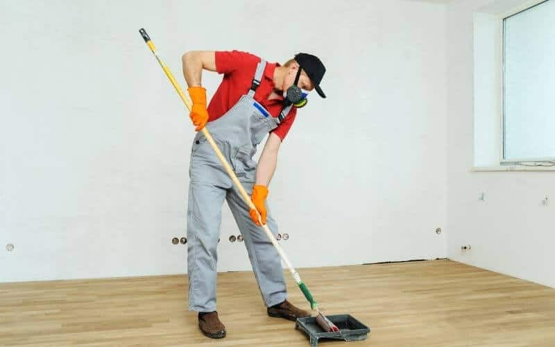 man cleaning up wood floor